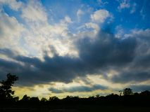 Storm Clouds Over The Sunset Horizon. Dramatic storm clouds over the sunset sky in a park in New Jersey Stock Photo
