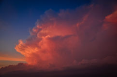 Storm clouds painted in pink by the setting sun. Pink sunset on a hot summer evening . Storm clouds painted in pink by the setting sun royalty free stock image