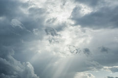 Storm Clouds Pierced by Sun Rays. Intense cloud formations. High contrast and slight grain used to give an ominous feeling to the image. Designed for use a Royalty Free Stock Images
