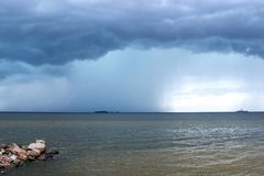 Storm clouds, rain and lightning over the sea royalty free stock images