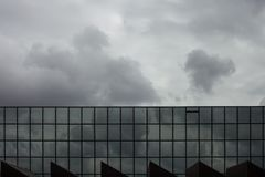 Storm clouds reflect in windows of office building/ Mirror windo Royalty Free Stock Image