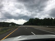Ominous clouds on the highway before rain. Storm clouds rolling in to the highway road stock photos