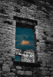 Storm Clouds Through the Ruins. Abandoned stone building with storm clouds through the windows royalty free stock image