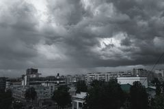 Storm clouds in the sky over the city. Gray gloomy sky before hurricane stock images