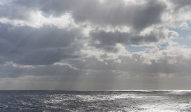 Storm clouds with sun rays on the ocean stock image