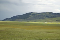 Storm clouds and sunlight on farm in distance of Centennial Valley, MT Royalty Free Stock Images