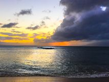 Storm Clouds Sunset Ocean. Gray storm clouds almost cover the blue sky as the sun sets with orange glow over a calm ocean stock images