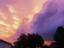 Storm clouds at sunset with silhouetted trees royalty free stock image