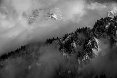 Storm clouds surround snowy mountains in the alps Royalty Free Stock Photography