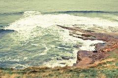 Storm at the coast. Rough sea crashing against coastal rocks in Scotland royalty free stock photos