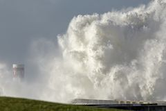 Storm on the coast. Storm on the portuguese north coast with huge waves invading piers and lighthouses against a beautiful blue sky Stock Images