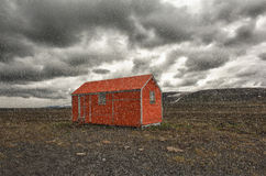Storm is coming. Old red snowstorm shelter can save a life in a cruel blizzard or in winter on Iceland Royalty Free Stock Photo