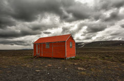Storm is coming. Old red snowstorm shelter can save a life in a cruel blizzard or in winter on Iceland Royalty Free Stock Image
