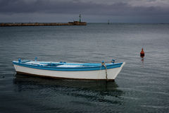 Storm is coming. In the background,Old wooden boat tied in the harbor in Umag, Croatia in the foreground Stock Image
