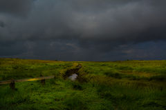 Storm coming. Storm clouds gather over coastal salt marsh in Lincolnshire with  fence in foreground and tidal creek Stock Photos