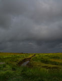Storm coming. Storm clouds gather over coastal salt marsh in Lincolnshire with  tidal creek,portrait Stock Photography