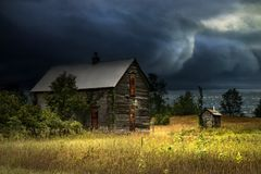 Storm Coming. Dark storm clouds over the water rolling in behind an abandoned wood house with boarded up windows Stock Images