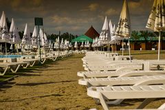 The storm is coming over the beach chairs and umbrella. Dramatic storm waiting scene with no people. Ramnicu Valcea, Romania - 22. stock images