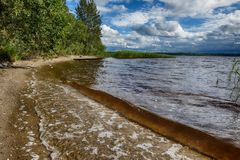 A storm is coming, so the wave on the lake will be large. A large lake with clear water and beautiful vegetation surprises our imagination, the lake is Stock Photography