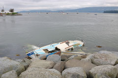 Storm Damage Aftermath. Remnants of a severe wind storm and a destroyed sailboat on the rocks Stock Photos