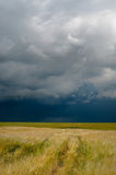 Storm dark clouds over field Stock Images
