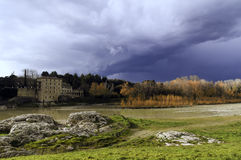 Storm dark clouds over field with building Royalty Free Stock Photography