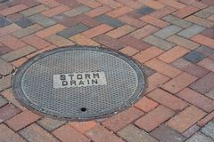 Storm Drain Cover on a Brick Road Royalty Free Stock Photos