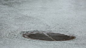 Storm Drain Manhole, Heavy Rain. Water from heavy rain flows through a manhole cover into a storm drain stock footage