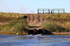 Storm drains front view. Storm drain pipes emptying water into a coastal estuary viewed from front Royalty Free Stock Photography