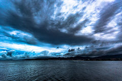 Storm dramatic clouds over land view from sea Royalty Free Stock Photo