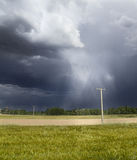 Storm in the fields. Black and cloudy sky during a storm in the green fields. The rain can be seen falling from the sky royalty free stock photos