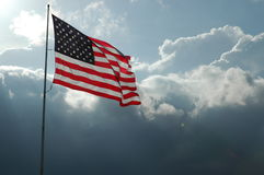 Storm Flag. Sun-washed star-spangled banner facing threatening storm clouds Stock Photography