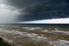 Storm front over water with wall of rain. In the centre Stock Image