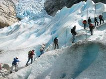 Storm of a glacier. Group of tourists is climbing to a glacier. Briksdal glacier,Jostedalsbreen national park, Norway Stock Images