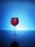 Storm in a glass of red wine on a blue background stock image