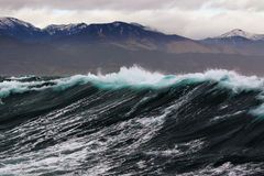 Storm. High the storm surge against the shore with snow-capped peaks royalty free stock photo