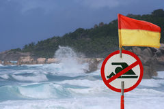 Storm, hurricane sea. Swimming alert sign. The big waves of the storm, hurricane are crushing on the beach with rocks and palm-trees. The alert red sign of royalty free stock photo
