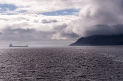 Before the Storm. Island in stormy clouds with the cargoship royalty free stock photography