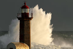 Storm in the lighthouse. Storm waves over lighthouse of the harbor  of river Douro, Portugal; end of the day light Royalty Free Stock Photo