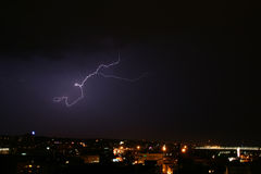 Storm and lightning over city. Dark clouds and shiny lightning over large city royalty free stock image