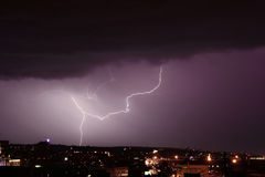 Storm and lightning over city. Dark clouds and shiny lightning over large city royalty free stock photo