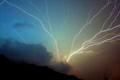 Storm lightning strikes. Detailed storm lightning strikes with numerous branches striking in the mountain Stock Photo