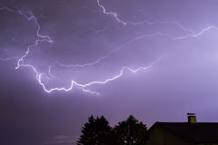 Storm with lightnings, a house and trees Royalty Free Stock Photos