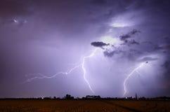 Storm med blixt i landskap Arkivbild