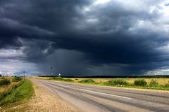 Storm near the country road. Rain clouds near the country road. A thunderstorm expected Royalty Free Stock Photo