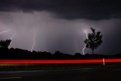 Storm och blixt på natt I , på vägen Royaltyfri Bild