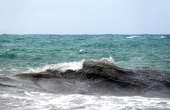 Storm in the open sea in gloomy summer day. The wave with white foam splashing on the foreground Royalty Free Stock Image