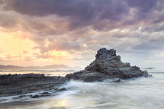 The storm over the coast is getting over. Seascape showing waves breaking against a rock on the coast with a cloudy stormy sky and the sun appearing in the Stock Photography