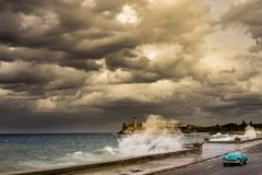 Storm Over Malecon Cuba. Stormy weather over the Malecon in La havana, Cuba, with car passing by Royalty Free Stock Photography