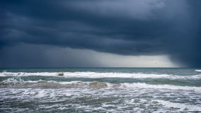 Storm over the ocean. Single bird flies between two rain shafts. South Padre Island, Texas Royalty Free Stock Photos